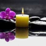 Eine Kerze mit schwarzen Steinen im Wasser mit Lotusblüte
