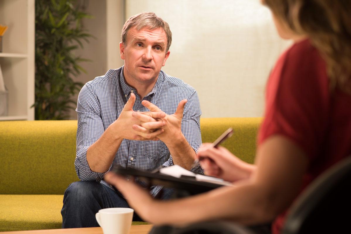 Ein Mann sitzt auf einem Sofa und unterhält sich mit einer Frau, die sich Notizen macht.