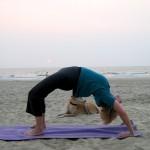Eine Frau macht Yoga am Strand